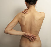 Backache pain. Backache of young woman with hand on back Royalty Free Stock Image