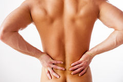 Backache. Rear view of young muscular man touching his back while standing against white background Stock Photo