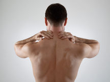 Backache. Sportsman with backache on gray background Royalty Free Stock Photos