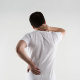 Backbone disease. Young male in white t-shirt suffering from neck and back pain. Osteoporosis therapy. Lumbago treatment Royalty Free Stock Image