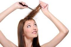 Backcombing long brunette female hair Stock Photo