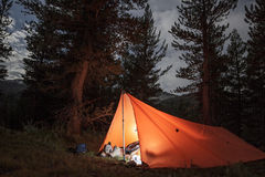 Backcountry camping in a lit tarp tent. Campsite lit by headlamp in the backcountry of Yosemite National Park royalty free stock images