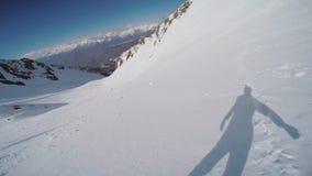 Backcountry Fahrt des Snowboarders von der Spitze des schneebedeckten Berges Sonniger Tag drehzahl stock video