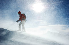Backcountry skier. A lonely backcountry skier reaching the summit of the mountain during a snowstorm, horizontal orientation stock images
