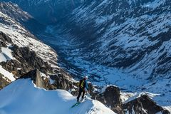 Backcountry skier peering over the steep edge of a summit ridge into the Bartholf Creek drainage. Backcountry skier athlete looking over steep cliff into the royalty free stock photo