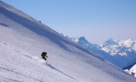 Backcountry skier skiing really fast down an untouched mountain side with loads of fresh powder snow Stock Image