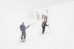 Backcountry skiers ascending in the fog Royalty Free Stock Photography