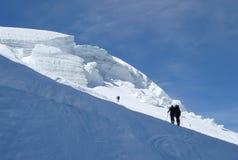 Backcountry-Skifahrer, die oben einen steilen Gletscher und in das Sonnenlicht auf ihrer Weise zu einer hohen alpinen Spitze nahe Stockfotografie