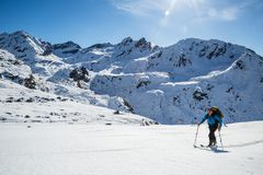 Backcountry skiing in Alaska on a bright sunny day in spring time. Backcountry skier hiking uphill on a bright sunny day in the Alaskan backcountry. Spring stock images