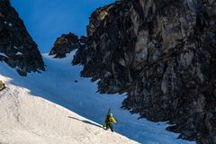 Skier hiking or bootpacking a steep couloir or chute between two rock cliffs in the backcountry of the Talkeetna Mountains in. Backcountry skiing in Alaska, a stock photo