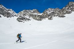 Backcountry skiing in the Talkeetna Mountains of Alaska. Skier moving uphill under large cliff bands in Hatcher Pass area. Backcountry skier hiking uphill under royalty free stock photos