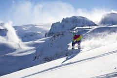 Backcountry snowboarder riding fresh powder. Snowboarder in backcountry cutting new lines in fresh snow stock photo