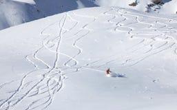 Backcountry snowboarder riding fresh powder. Snowboarder in backcountry cutting new lines in fresh snow stock photos