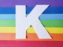 Letter K in white with background in rainbow colors. Backdrop for ads related to colors and lgbt community, graphic sign of a writing system with multicolor stock photo