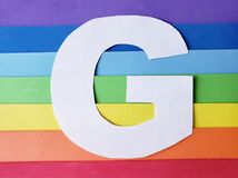 Letter G in white with background in rainbow colors. Backdrop for ads related to colors and lgbt community, graphic sign of a writing system with multicolor stock image