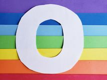 Letter O in white with background in rainbow colors. Backdrop for ads related to colors and lgbt community, graphic sign of a writing system with multicolor stock photography