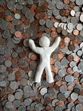 Figure of a person resting in money, made with white clay and background with dollar pennies. Backdrop for announcements of trading and exchange, bank and royalty free stock photography