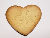 Heart shaped baked biscuit, background and texture. Backdrop for confectionery and cafeteria ads, made from sweet flavored baked pasta, flour based baked food royalty free stock photography