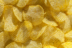 Backdrop of delicious potato chips with onion. Closeup. Backdrop of delicious rippled potato chips with onion. Closeup stock photos