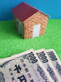 Japanese banknotes, figure of a house on green surface and blue background. Backdrop for mortgage and housing value ads, loan for home construction and stock photos