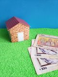 Uruguayan banknotes, figure of a house on green surface and blue background. Backdrop for mortgage and housing value ads, loan for home construction and royalty free stock photos