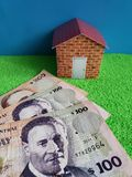 Uruguayan banknotes, figure of a house on green surface and blue background. Backdrop for mortgage and housing value ads, loan for home construction and stock images