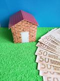 European banknotes, figure of a house on green surface and blue background. Backdrop for mortgage and housing value ads, loan for home construction and stock images