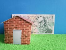 Czech banknote, figure of a house on green surface and blue background. Backdrop for mortgage and housing value ads, loan for home construction and remodeling royalty free stock photos