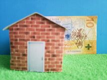 Swiss banknote, figure of a house on green surface and blue background. Backdrop for mortgage and housing value ads, loan for home construction and remodeling stock images