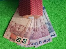 Brazilian banknotes, figure of a house on green surface, view from above. Backdrop for mortgage and housing value ads, loan for home construction and remodeling royalty free stock image