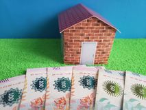 Argentine banknotes, figure of a house on green surface, view from above. Backdrop for mortgage and housing value ads, loan for home construction and remodeling royalty free stock photo