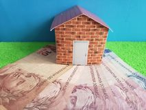 Brazilian banknotes, figure of a house on green surface and blue background. Backdrop for mortgage and housing value ads, loan for home construction and stock image