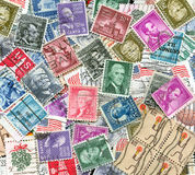 Backdrop of old U.S. postage stamps. Background of miscellaneous old used vintage U.S. postage stamps Stock Photo