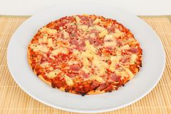 Backed pizza with pinapple and ham. A backed pizza with pinapple and ham Royalty Free Stock Photo