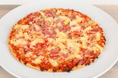Backed pizza with pinapple and ham. A backed pizza with pinapple and ham Royalty Free Stock Images