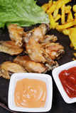 Backed spicy wings with chips closeup Stock Image