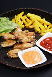Backed spicy wings with chips Royalty Free Stock Photo