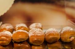 Backed yeast bun row with powdered sugar Royalty Free Stock Photos