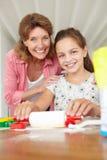 Backen des jungen Mädchens mit Großmutter zu Hause Lizenzfreies Stockfoto