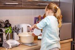 Backen des kleinen Mädchens waffles in der Küche nach einem Rezept auf dem Smartphone Stockbild