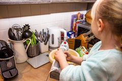 Backen des kleinen Mädchens waffles in der Küche nach einem Rezept auf dem Smartphone Stockbilder