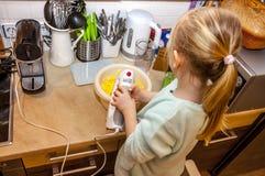 Backen des kleinen Mädchens waffles in der Küche nach einem Rezept auf dem Smartphone Stockfoto
