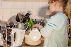 Backen des kleinen Mädchens waffles in der Küche nach einem Rezept auf dem Smartphone Stockfotos