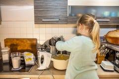 Backen des kleinen Mädchens waffles in der Küche nach einem Rezept auf dem Smartphone Lizenzfreie Stockfotografie