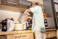 Backen des kleinen Mädchens waffles in der Küche nach einem Rezept auf dem Smartphone Lizenzfreies Stockbild