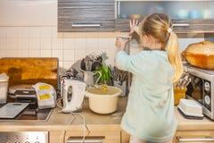 Backen des kleinen Mädchens waffles in der Küche nach einem Rezept auf dem Smartphone Stockfotografie
