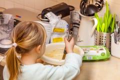 Backen des kleinen Mädchens waffles in der Küche nach einem Rezept auf dem Smartphone Lizenzfreies Stockfoto