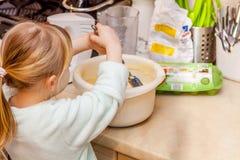 Backen des kleinen Mädchens waffles in der Küche nach einem Rezept auf dem Smartphone Lizenzfreie Stockfotos