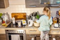 Backen des kleinen Mädchens waffles in der Küche nach einem Rezept auf dem Smartphone bei der Stellung auf einem Stuhl Stockbilder