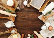 Backen- oder Rezeptbestandteileier, Mehl, Milch, Butter, Zucker auf Holztisch von oben lizenzfreies stockfoto
